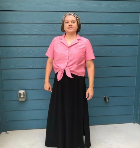 Rachel is standing in front of a house wearing a long black skirt and a pink-colored Gilbert top, which is collared, has three buttons, and ties at the front.