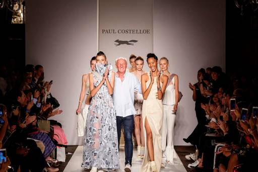 A group of female models walk onto the runway,  surrounding  the fashion designer Paul Costelloe at a fashion show. The models and audience applaud.