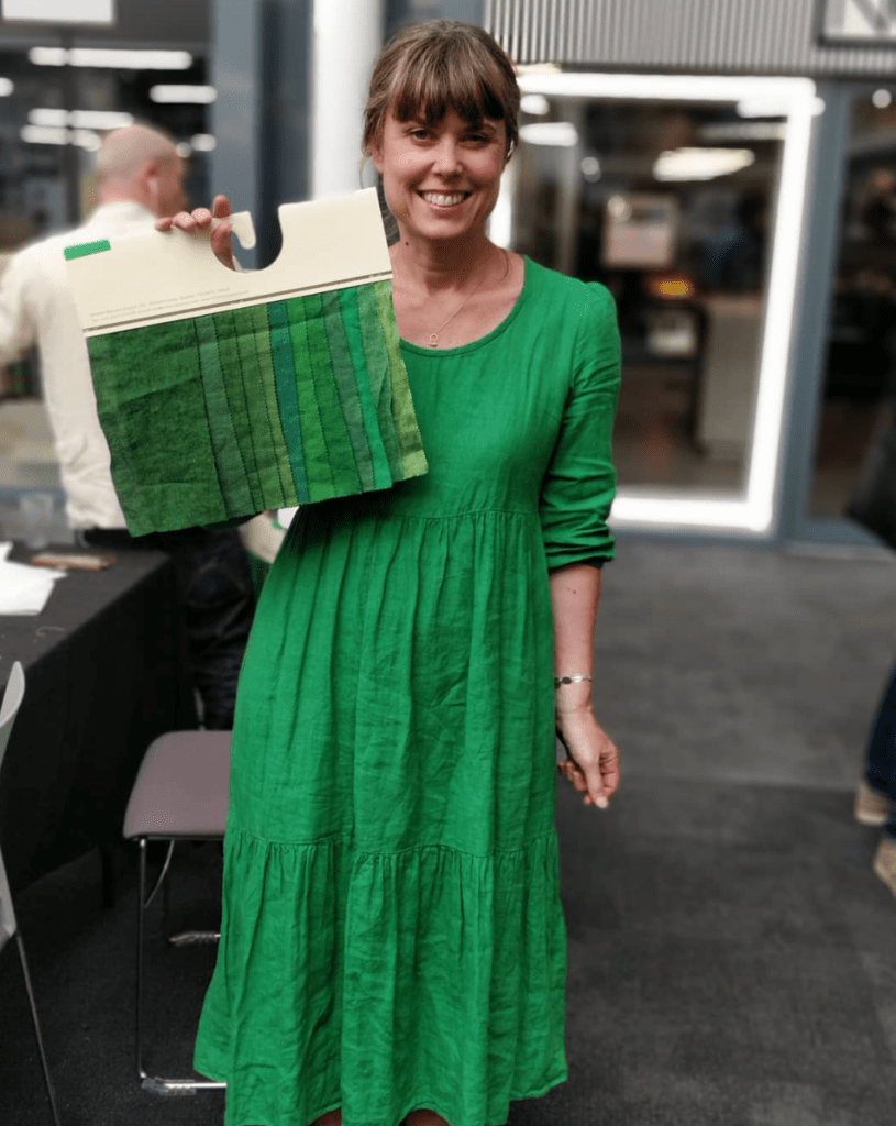 A young woman stands in a studio setting. She wears a green linen dress and holds a  shade card with several  samples of linen swatches in different shades of green.