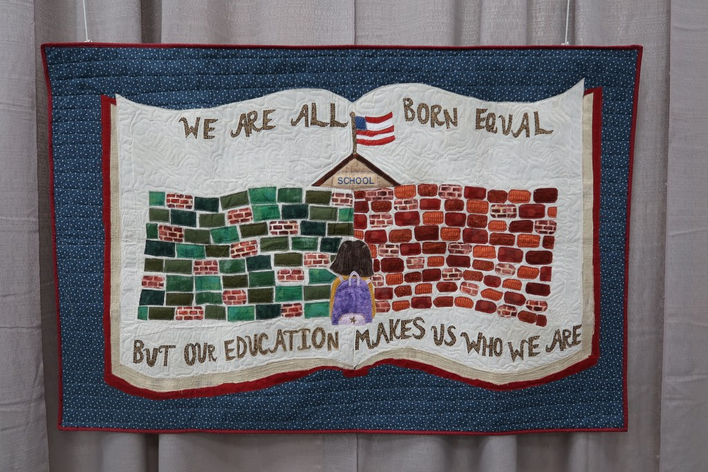 """A horizontal quilt with a blue background and an open book shown on it.  The book shows a school behind a wall with a student standing in front of it.  The text reads """"we are all born equal but our education makes us who we are""""."""