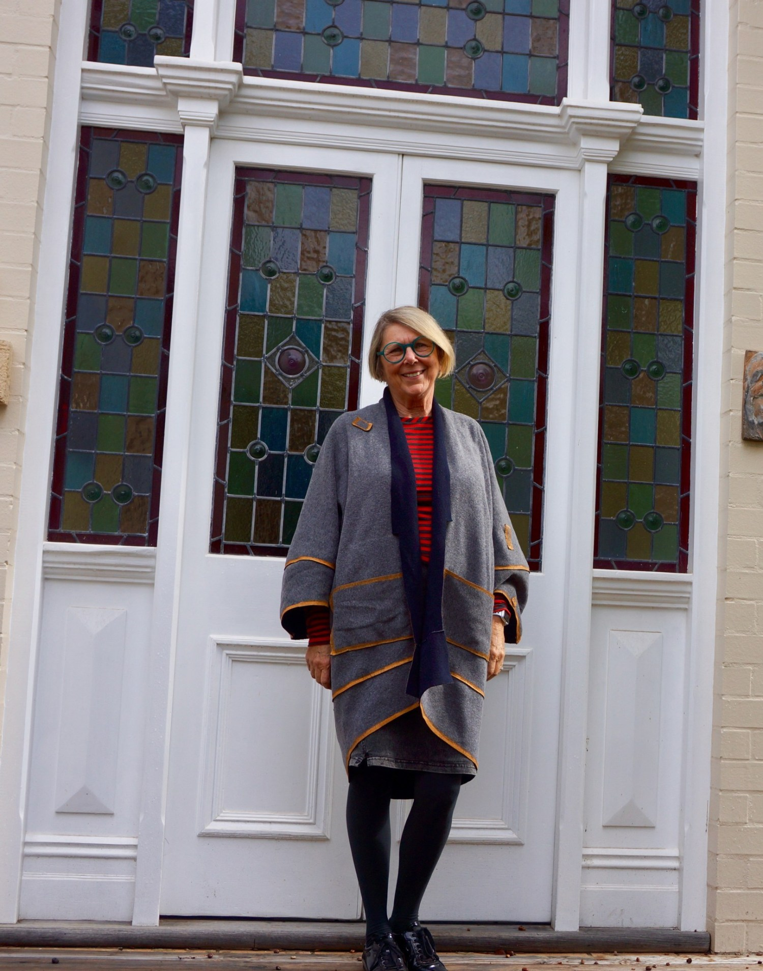 Sue stands in front of a white door with stained glass panels. She wears the 'nog coat' described in the post.