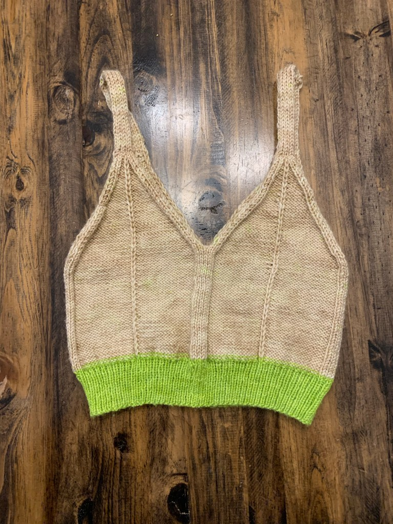 Hand-knit bralette in neutral beige overall with a wide neon green hem.