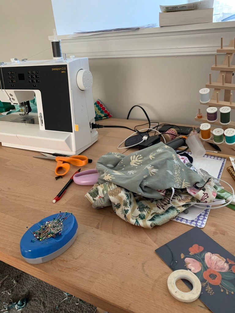 Sewing table with a small pile of fabric and various sewing implements scattered on it