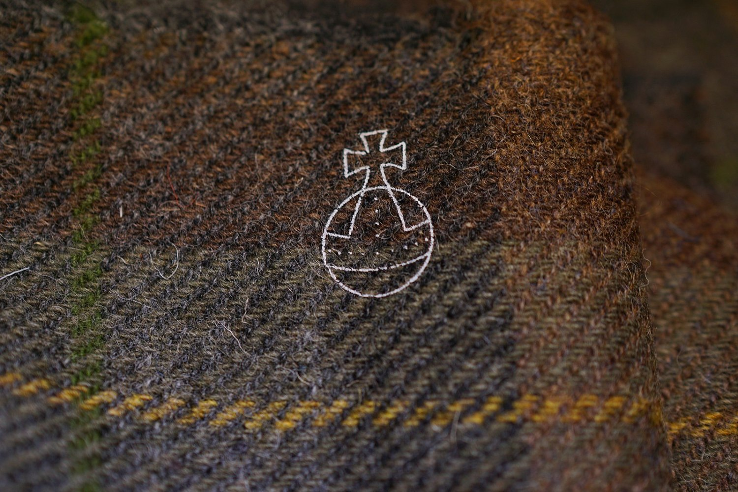 A close up of Harris Tweed cloth, with browns, grays, yellow, and green. A white outline of the Orb and Cross logo is on the fabric.