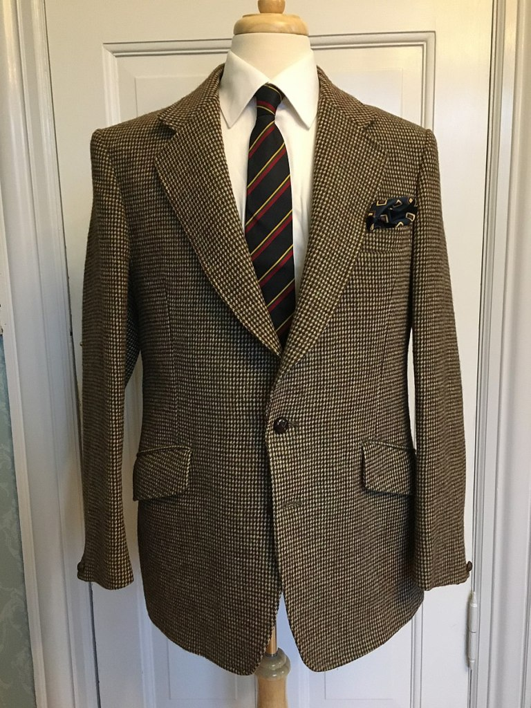 Jacket from Dunn & Co made from Harris Tweed, on a dress form with a shirt and tie.