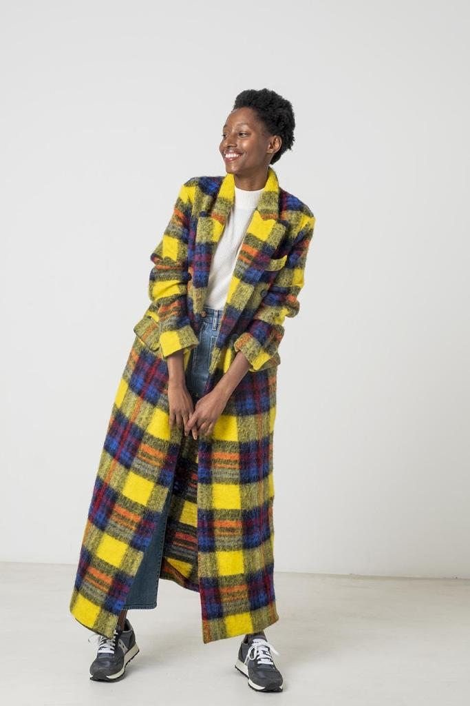 A black woman wearing an ankle length coat that has lapels and pocket flaps. The coat has a bold, plaid design and is blue, yellow, gray, and orange.