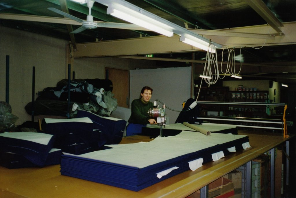 Image of a woman bulk cutting school uniforms in a factory