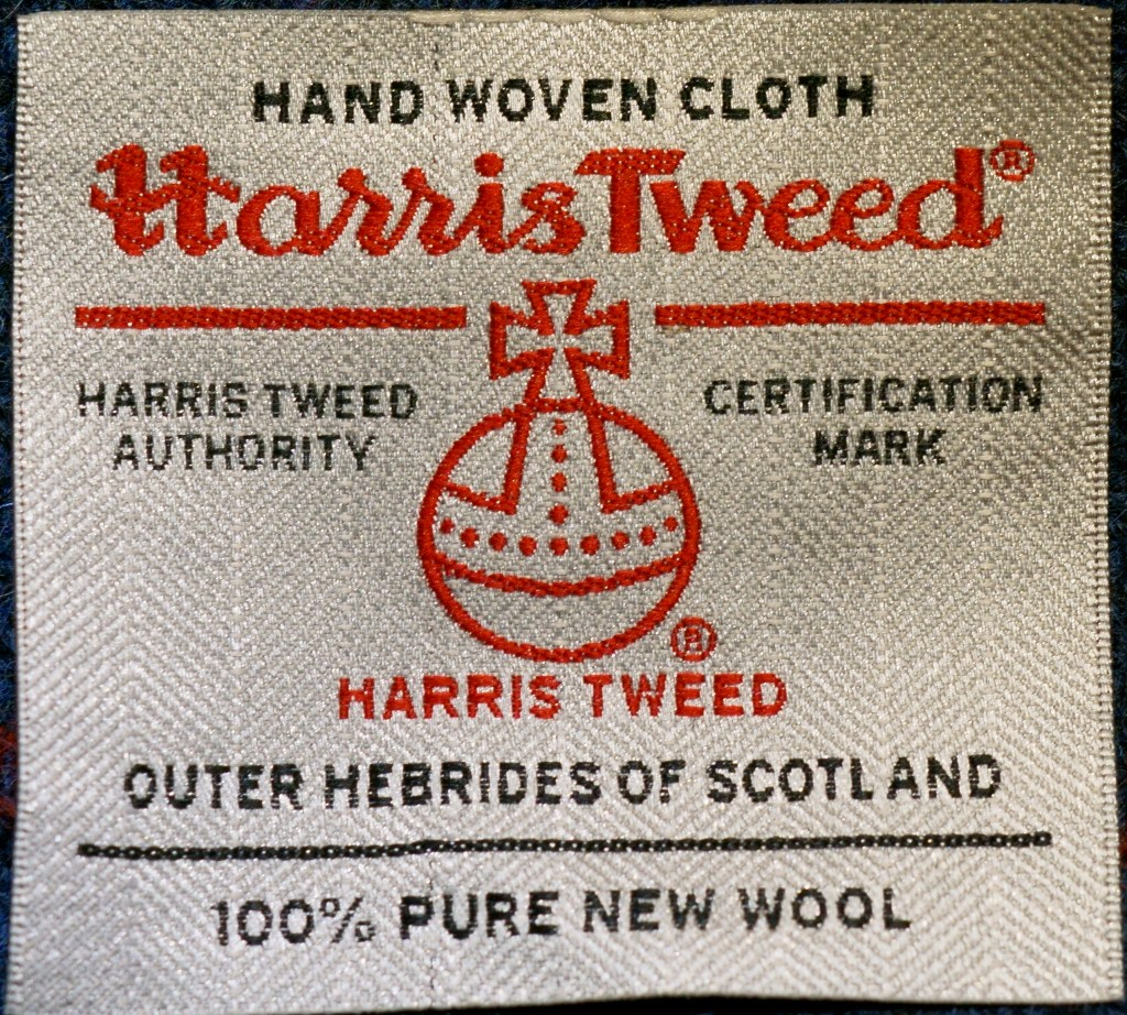 "A Harris Tweed label with red and black machined embroidery. ""Hand woven cloth"", ""Harris Tweed Authority"", ""Certification Mark"", ""Outer Hebrides of Scotland"" , and ""100% pure new wool"" are in black text. The label features registered trademark symbols and the Orb and Cross logo."