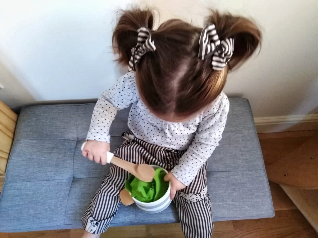 Image is looking down at a one year old child with long brown hair in pigtails sitting on chair playing with a wooden spoon and bowl. Child wears a black and white stripped hair bow in front of each pigtail, black and grey stripy trousers, and a black and white polka dot top.
