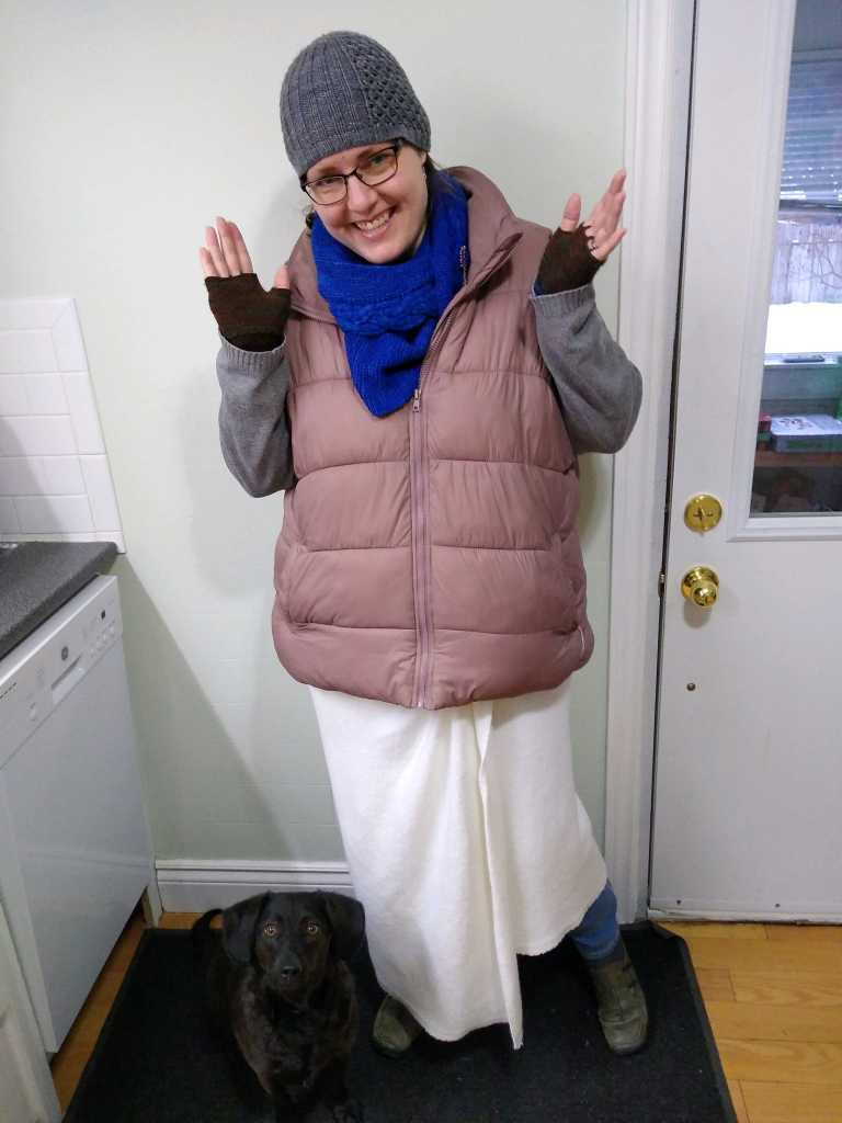 Anne stands in front of a door and kitcehn appliance, wearing puffer jacket, blanket, mitts, hat and scarf. Her small black dog sits looking up at the camera.
