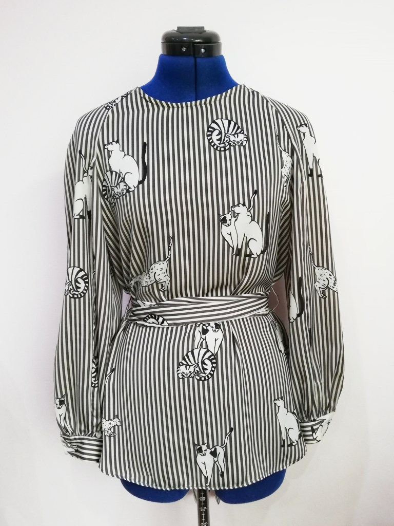Adult size blouse on mannequin. Blouse is long sleeved, length to the low hip, has a tie waist and has a high neck. The blouse is made from fabric that is black and grey striped with big cat illustrations.