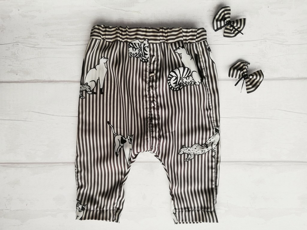 Image of finished trousers laid flat and two matching hair bows all made from reused black and white striped fabric with large cats.