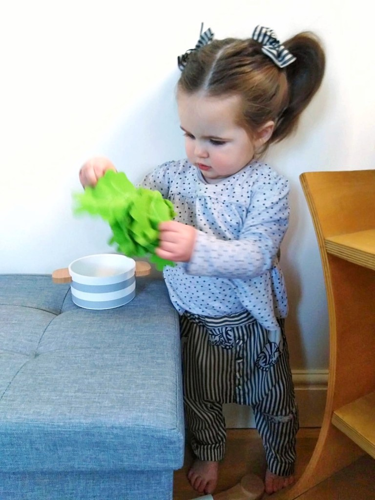 Photo shows 'Little M', a one year old child with long brown hair in pigtails. Little M is wearing the lounge trousers and the two hair bows placed in front of each pigtail. Little M is playing with children's kitchen toys.