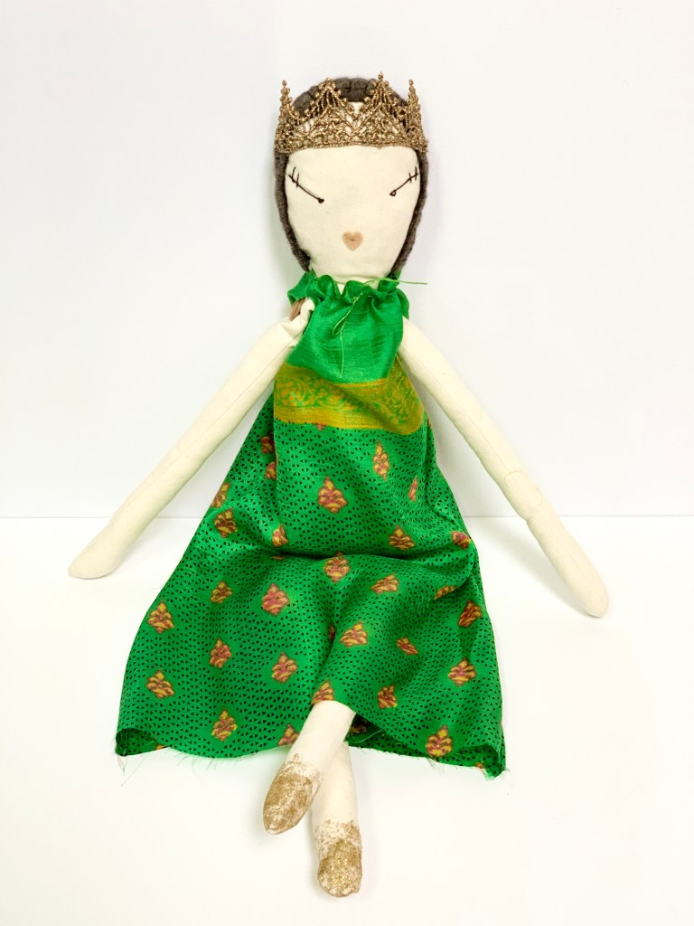 The rag doll with the green dress sits facing the camera.
