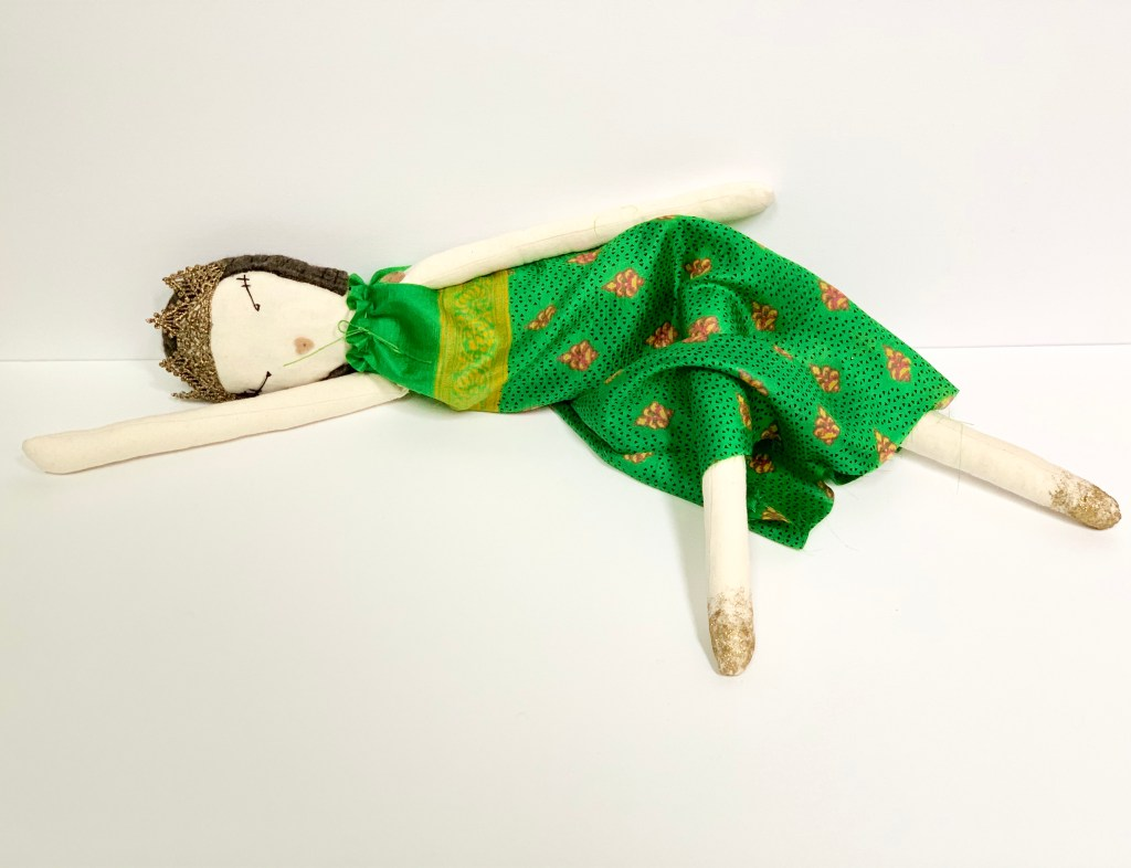 The doll with green dress is lying down, to suggest it is sleeping.