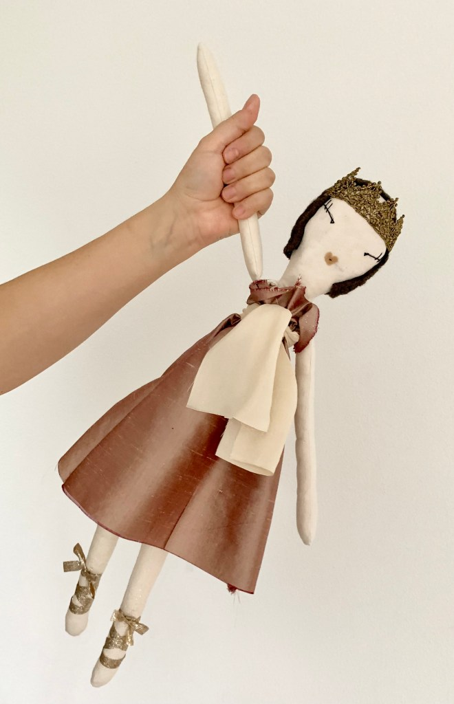 A hand holds a rag doll by it's arm. The doll has a white cloth body, a pink silk dress, gold trim tiara and gold straps on the feet to suggest ballet shoes.
