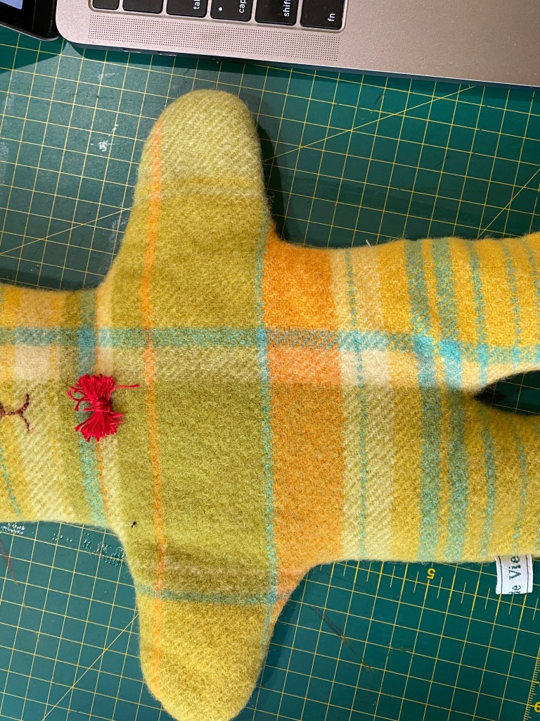 Wool teddy made from recycled blanket with an embroidered face and red bow tie.