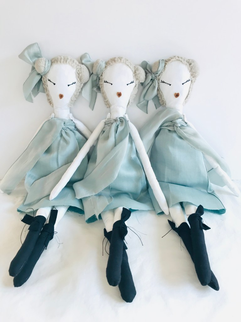 Three rag dolls wearing pale blue dolls sit together.