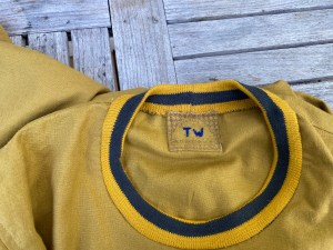 iInside the neck of a mustard linen tee shirt, with a hand embroidered label.