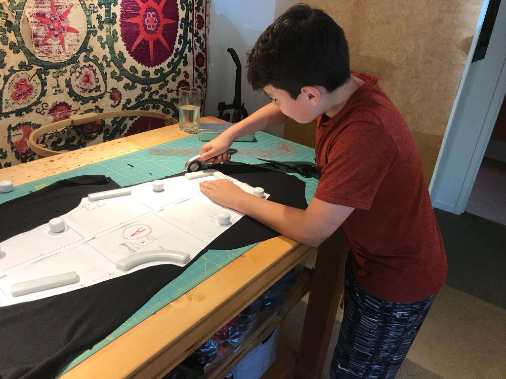 A teenage boy cutting a pattern piece out of black fabric with a rotary cutter