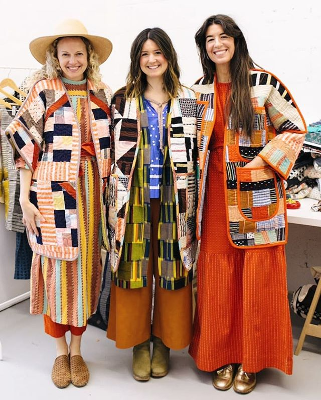 Image of three people standing close together all wearing one-of-a-kind, colourful quilted jackets made out of patches of fabric.