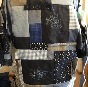 jacket made from predominantly blue scraps some of which have been embellished with floral embroidery