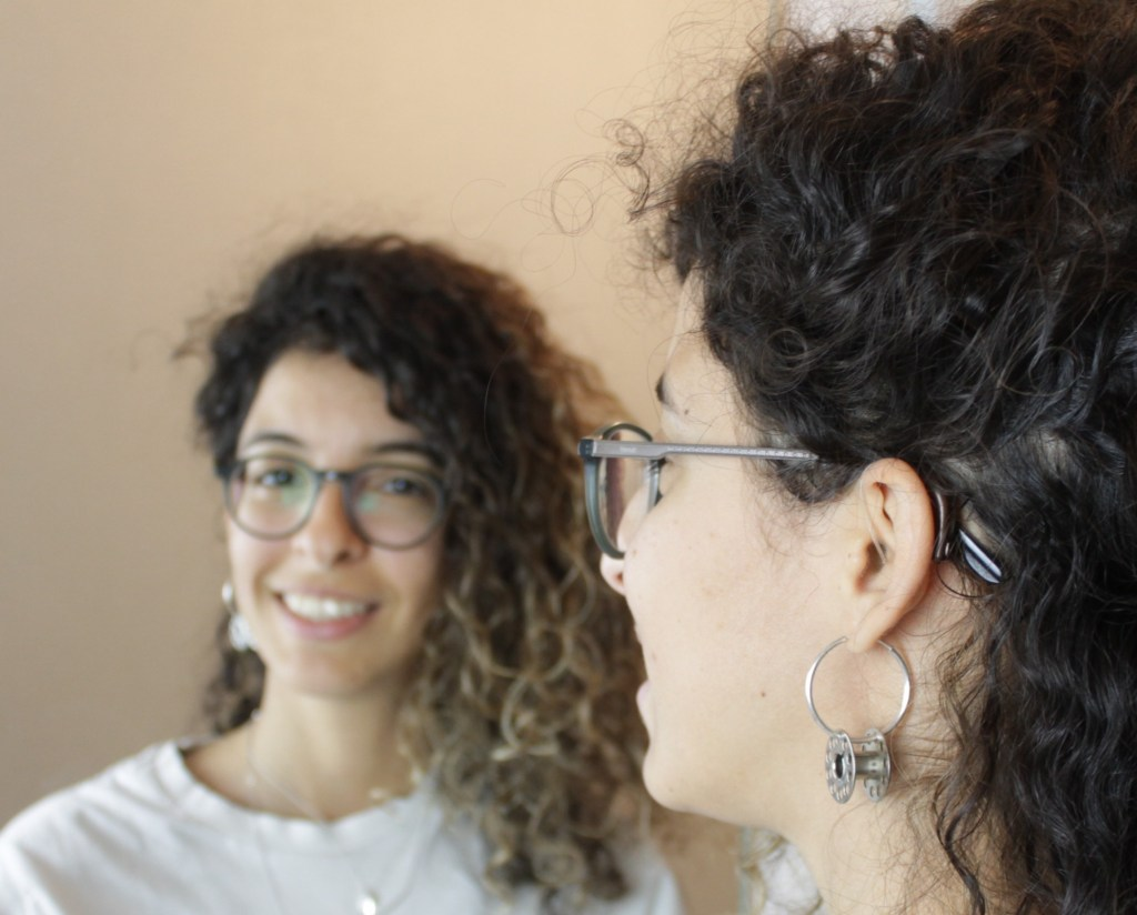 Anissa is shown in front of a mirror. You can see that they are wearing a white shirt, glasses, an small hoop earring with a thread bobbin, and their hearing aid.