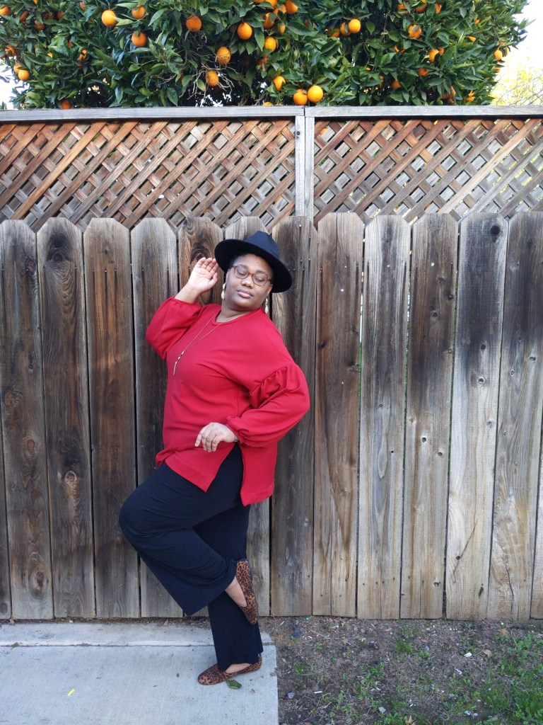 Image of a Black woman wearing a black hat and glasses sitting in front of a tall fence. Behind her, there is an orange tree full of oranges. She is wearing a bright red long-sleeved shirt, dark blue pants, and leopard-print flats.