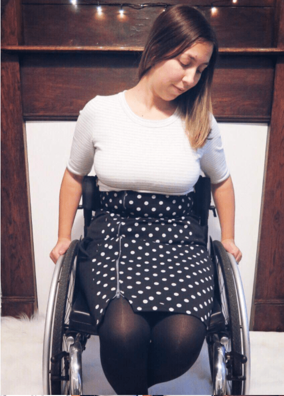 A person is shown sitting in a wheelchair, with hands on the pushrings.  they are wearing a black skirt with white spots on it and a white top with elbow length sleeves.  The skirt has an exposed zip running up the wearers right hand side.  They are looking away from the camera.