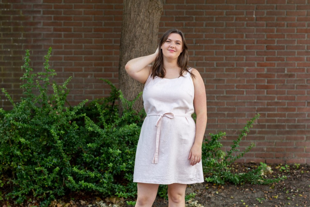 Brianna, a white woman with straight brown hair, wears a very pale pink sleeveless dress with a self belt. She is outdoors, standing in front of some trees and shrubs against a brick wall.
