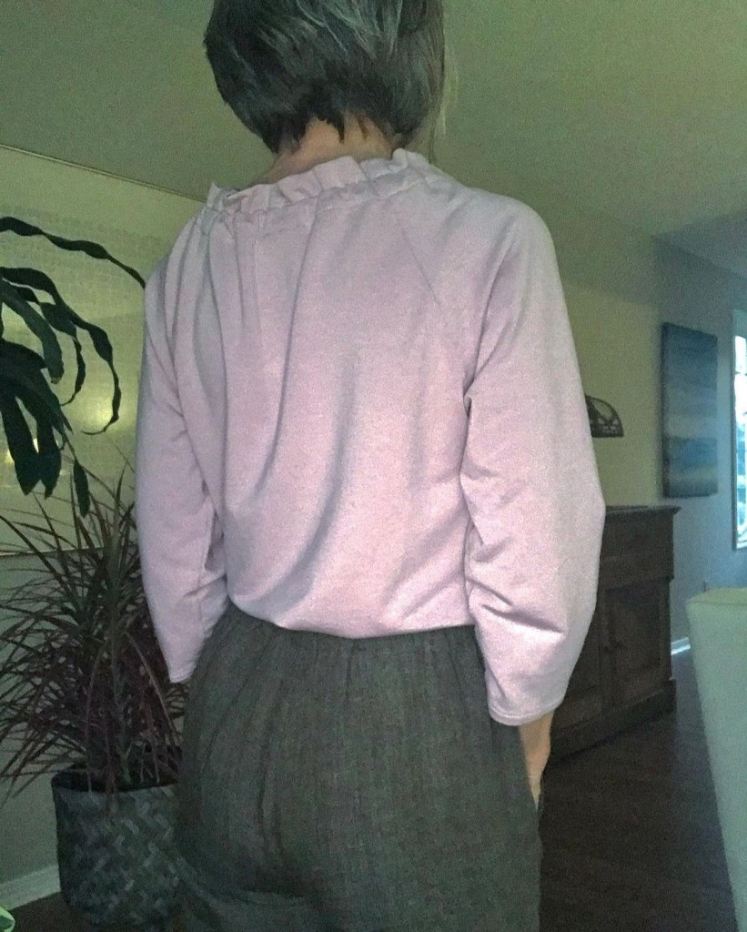 A woman standing in grey pants showing her butt