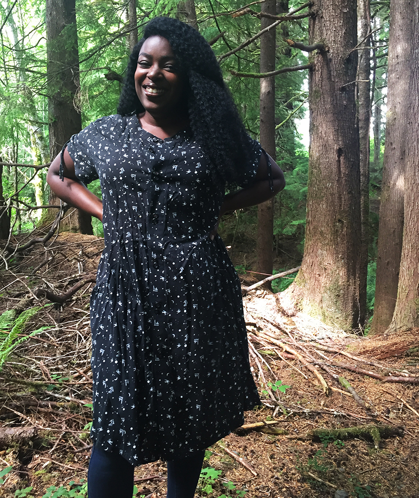 A black woman with long hair stands in the forest, arms akimbo, smiling at the camera. She is wearing a handmade grunge-style dress in black with swallow and star print.