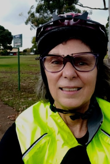 Karey is seen wearing a black shirt with a neon yellow safety vest. She is also wearing a bike helmet and purple glasses.