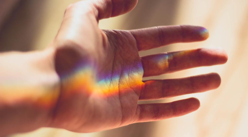 rainbow light projected on hand, palm facing out,