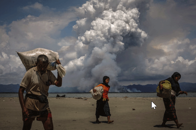 Smoke is seen on the Myanmar border as Rohingya refugees walk on the shore after crossing the Bangladesh-Myanmar border by boat (Part of Reuters series that won Pulitzer for feature photography)