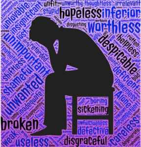 A silhouette of someone sitting on a chair with their head bowed and words of discouragement all around them.