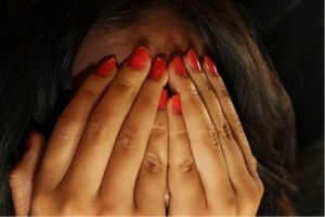 a woman hiding her face from the stigma of addiction.