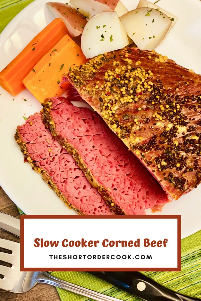 Slow Cooker Corned Beef on cutting board with carrots and potatoes