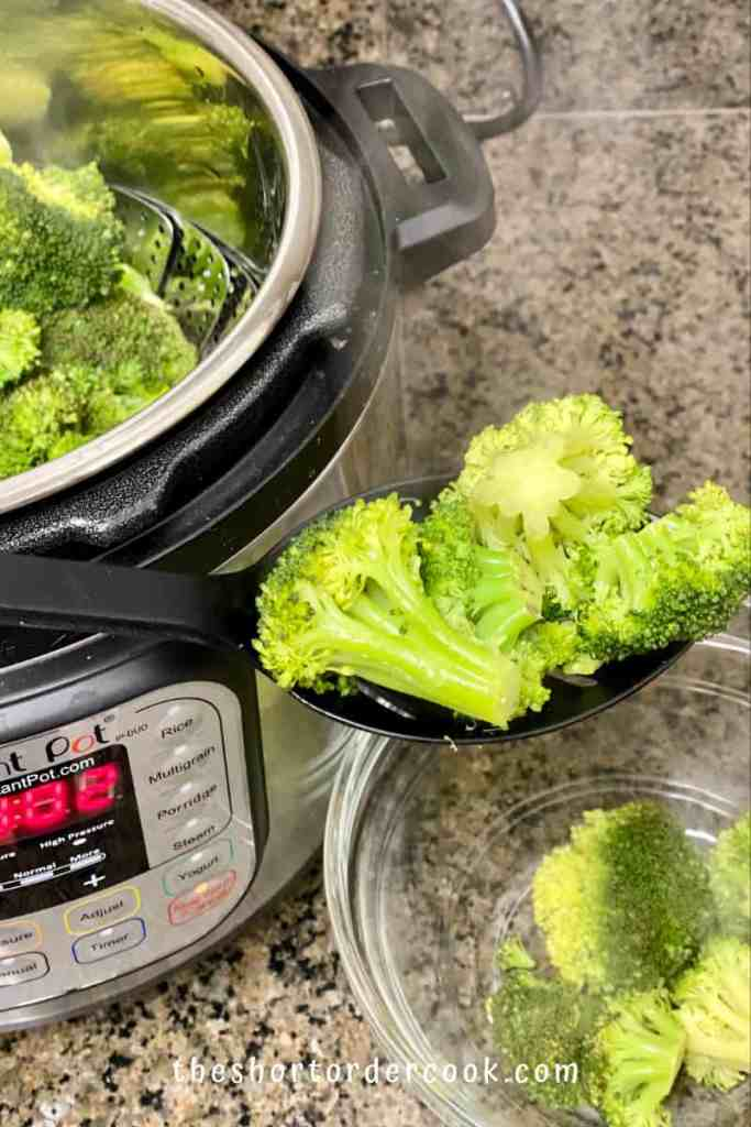 Instant Pot Steamed Broccoli spooning out broccoli from the insert