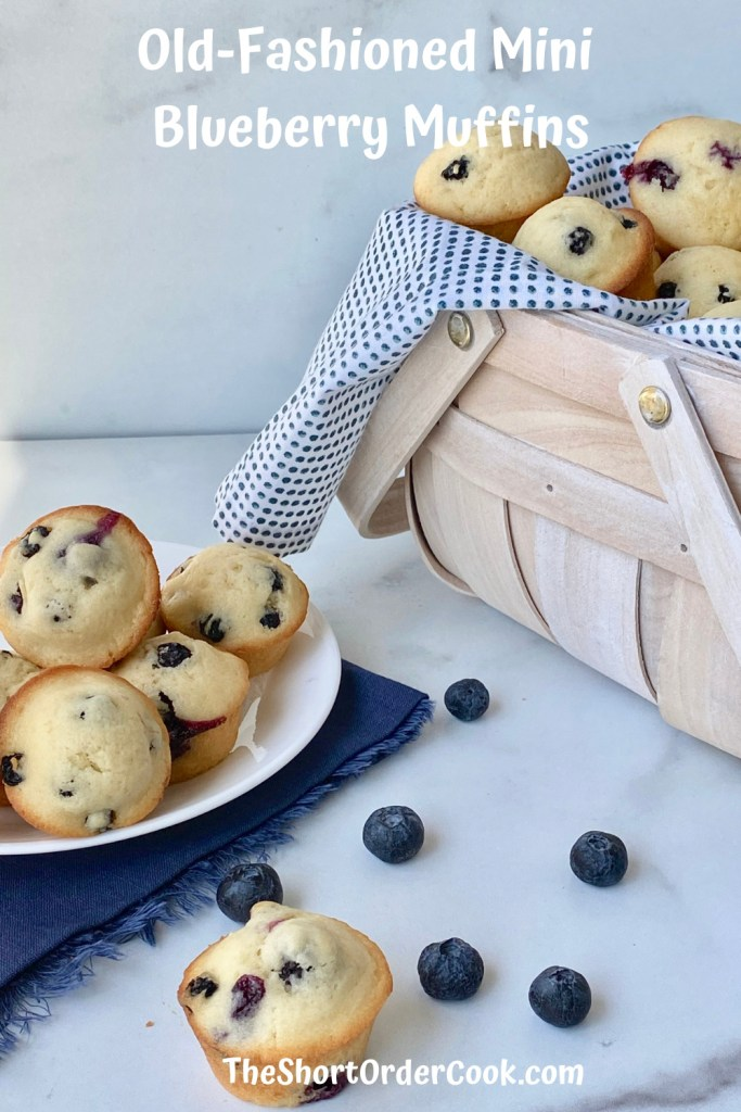 Old-Fashioned Mini Blueberry Muffins PN1 a basket with a cloth napkin and blueberry muffins in the background with a plate piled with blueberry muffins and one muffin on the marble top with a few stray blueberries