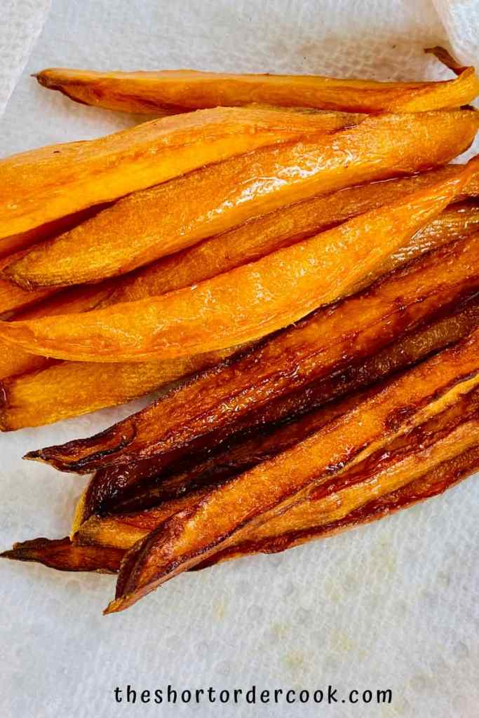 Deep Fried Sweet Potato Fries two batches of sweet potato fries on a paper towel lined dish one after the first fry and still bright orange and the second is brown after second fry