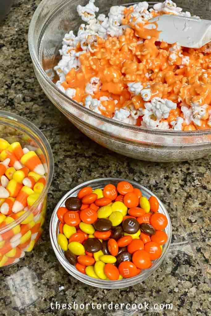 Halloween Popcorn Balls candies ready and orange marshmallow added to the popcorn