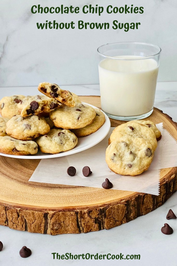 Chocolate Chip Cookies without Brown Sugar PN1 a wood slab with a plate of cookies stacked on top and a few cookies to the side and a glass of milk