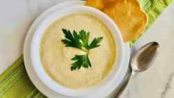 Instant Pot Cream of Celery Soup featured overhead of bowl full of soup topped with parsley sprig and crackers to the side and a spoon on the right all on top a green cloth napkin recipe card image