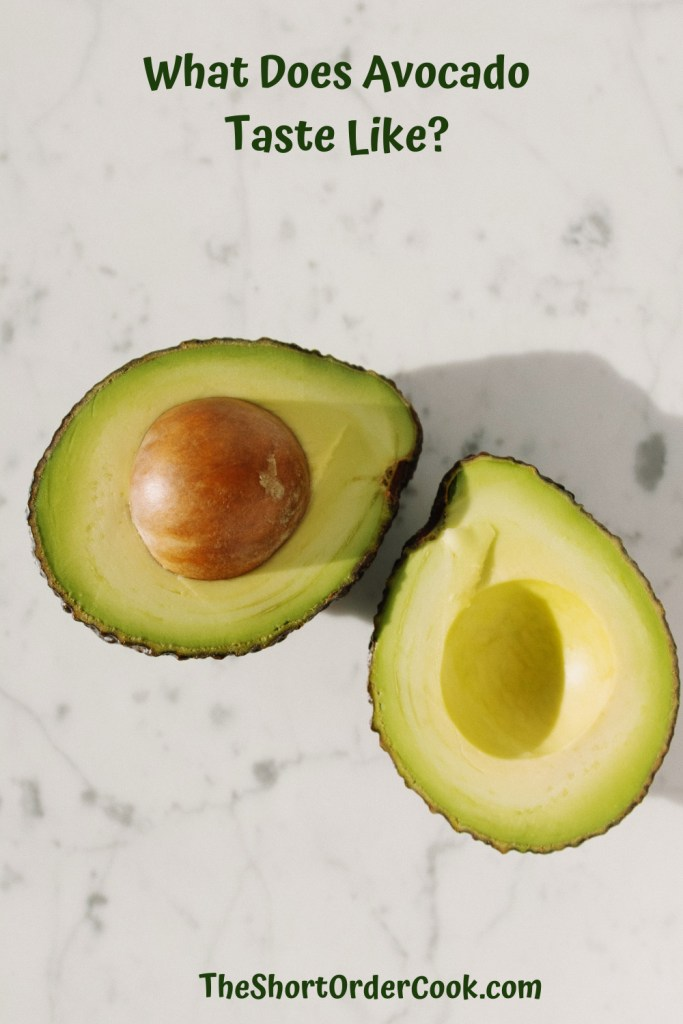 What Does Avocado Taste Like? PN1 an avocado cut in half exposing the pit and flesh sitting on a white countertop