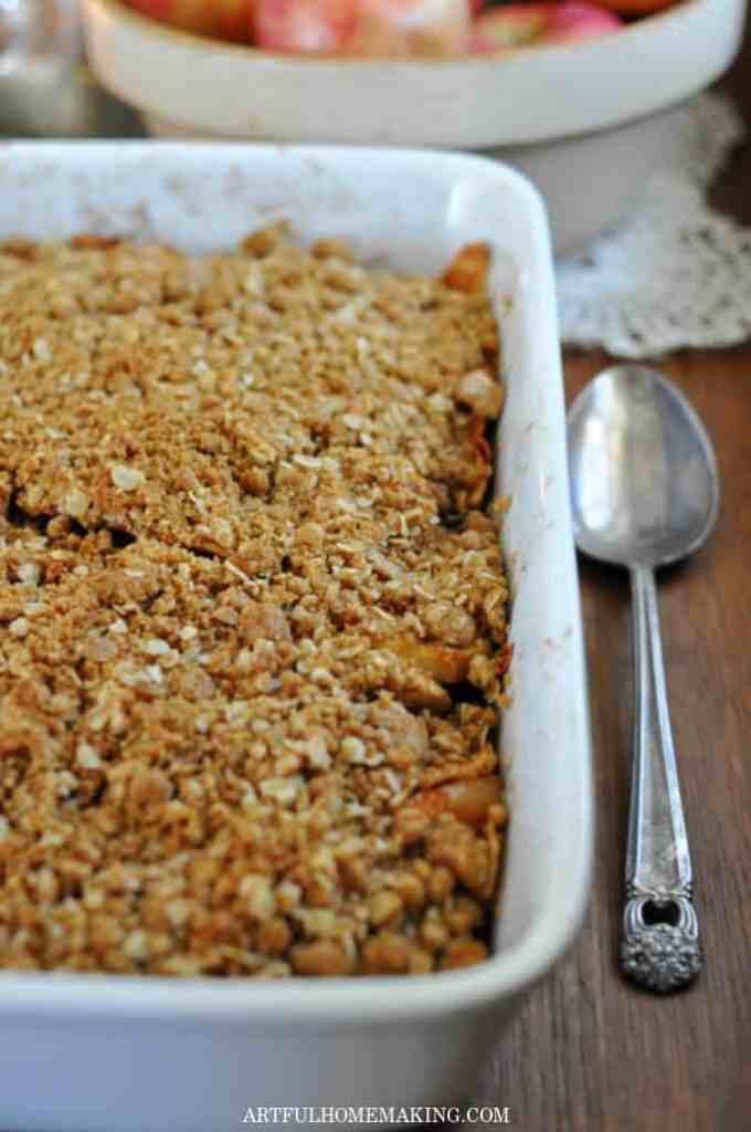 white casserole dish with apple crisp and a serving spoon