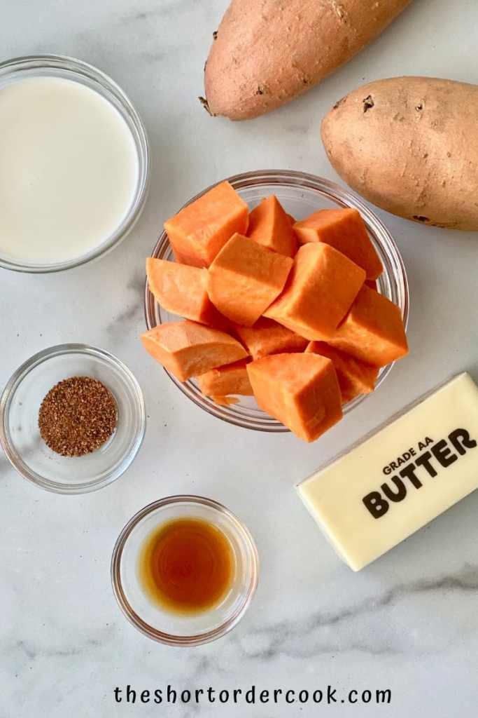 Whipped Sweet Potatoes ingredients on a table sweet potatoes and bowls filled with cream nutmeg vanilla and a stick of butter and diced sweet potatoes