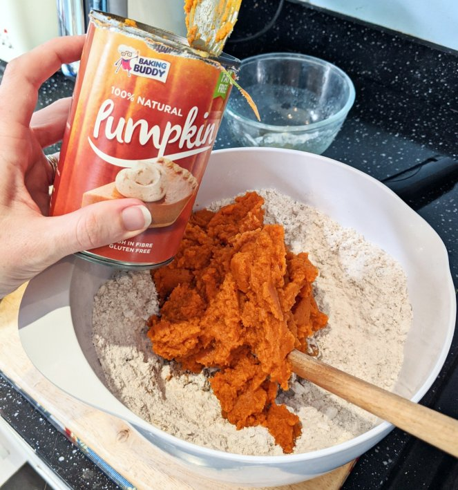 tinned pumpkin puree being mixed into a cake mix the sickly mama blog