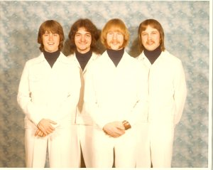 """Mick, Mark, Kim and Jon in matching white outfits. Some clubs at the time required matching clothes. This was our Beatles """"Your Mother Should Know"""" look!"""