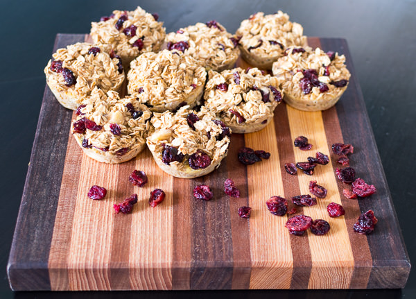 Oatmeal Banana Muffins on a cutting board with cranberries.